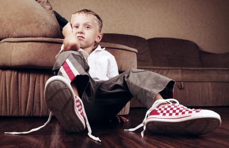 untied: Decepcionado ni�o peque�o con los cordones desatados en sus botas Foto de archivo