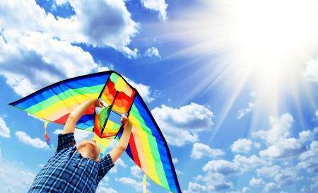 Happy kleine jongen vliegt een vlieger in de zonnige hemel