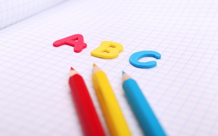 Close up image alphabet letters ABC on copybook page with colored pencils photo