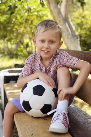 Cute boy with ball sitting on the bench at the park photo
