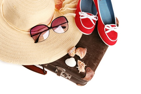 Chaussures chapeau de paille d'esprit rouges et de grandes lunettes de soleil rétro sur vieille valise
