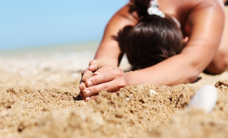 Closeup image woman hands in relaxation yoga pose at the sand beach photo