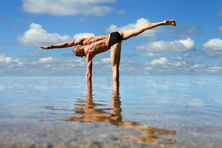 Muscular man doing lateral stretching yoga exercise into the sea water Stock Photo
