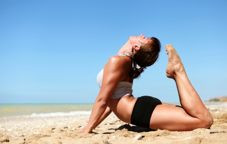Yoga practice. Young flexible woman doing full cobra yoga pose at the beach photo