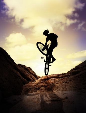 bike race: Silhouette  of young man on the mountain bike over purple sunset sky