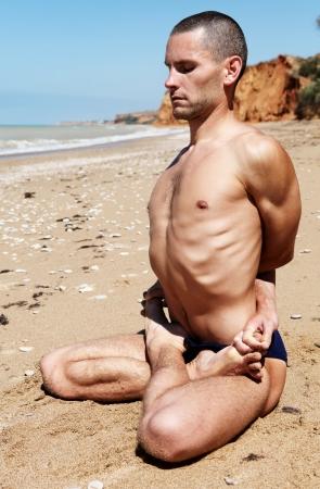 male torso: Yoga practice. Man in closed lotus yoga pose Stock Photo