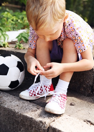 shoelace: Boy trying to tie lace on his sneakers sitting on the steps