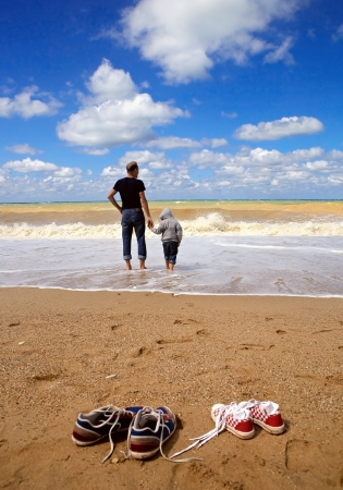 father and son: Father with son walk on the sea beach at the storm day Stock Photo