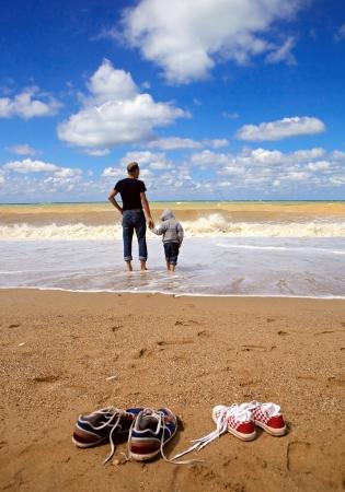 padre e hijo: Padre con el hijo en paseo de la playa del mar en el día de la tormenta