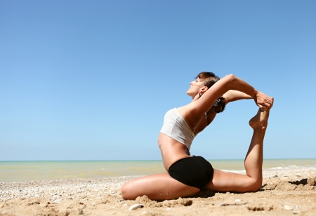 Yoga practice. Young girl doing king pigeon yoga pose on the beach photo