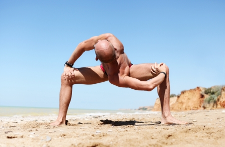 Yoga practice  Man doing strong spinal twist yoga pose at the sand beach photo