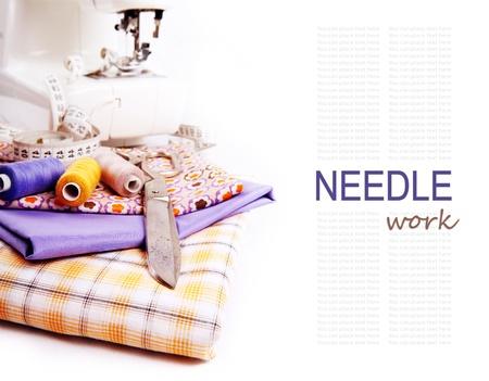 maquina de coser: Fondo blanco con tela de color, hilo de coser y otras herramientas
