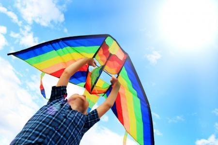 papalote: Llittle niño vuela una cometa en el cielo azul