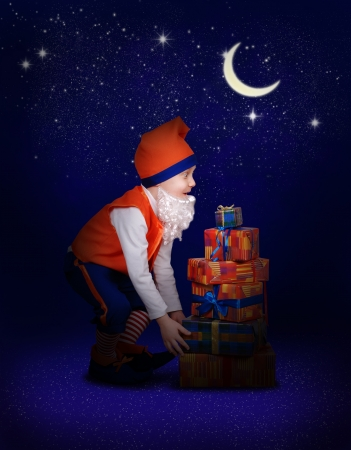 Surprised little gnome with gift boxes at the magic christmas night photo