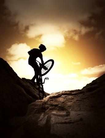 fiets: Silhouet van jonge man springen op de mountainbike Stockfoto