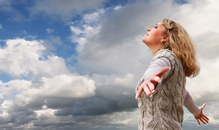 vast: Happy young woman with outstretched arms on the blue cloudy sky view Stock Photo