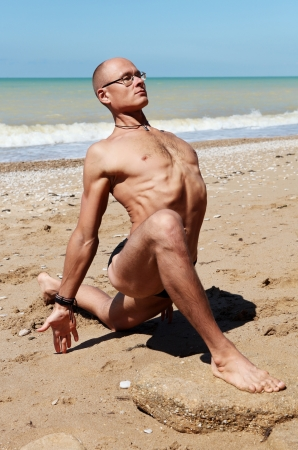 Yoga practice. Muscular man in King Pigeon Yoga Pose at the beach photo