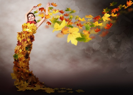 wind dress: Beautiful girl in dress from autumn leaves on  abstract windy background