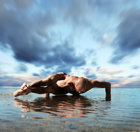 naked male body: Yoga into the water. Man doing eight arcs twisted pose