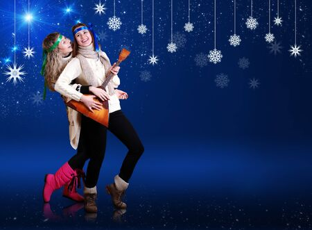 folk dancing: Happy girls with balalika dancing over dark blue background with snow flakes Stock Photo