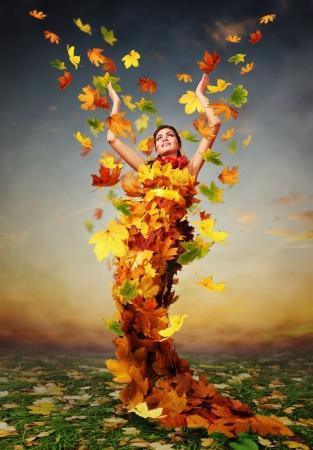 Piękna jesień pani w sukience z żółtych liści klonu
