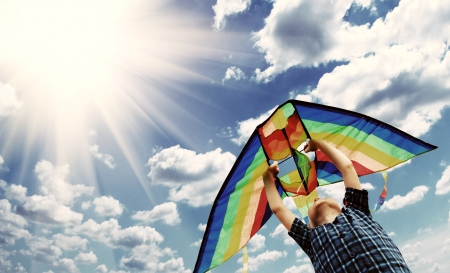 Happy little boy flies a kite in the sunny sky photo