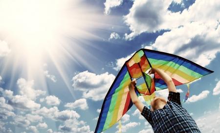 papalote: Niño feliz vuela una cometa en el cielo soleado Foto de archivo