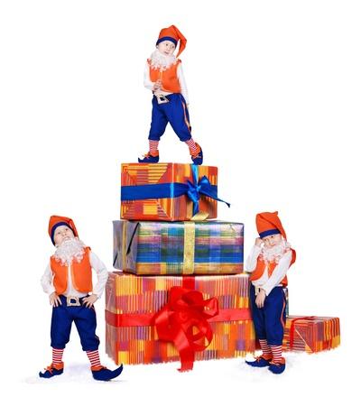 kabouters: Drie poseren kleine kabouters met cadeau dozen in de sneeuw