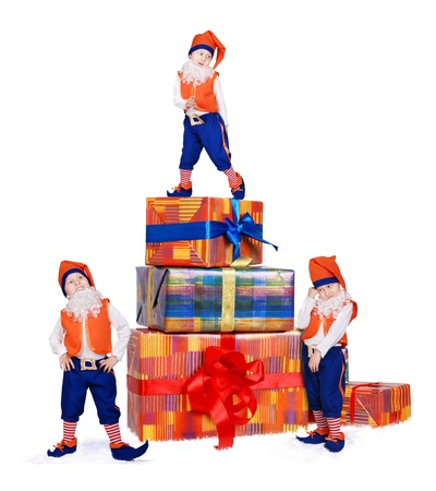 Three posing little gnomes with gift boxes in snow photo
