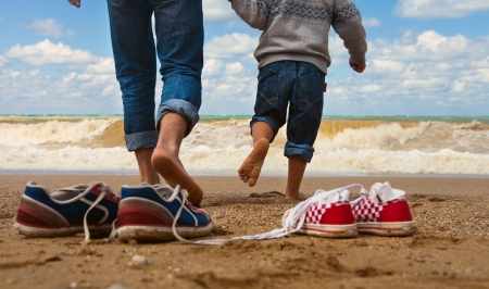 Close up image father and son legs walk at the seaside photo