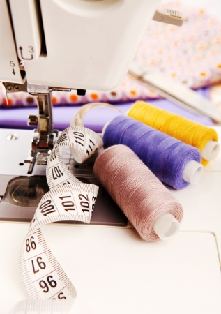sartorial: Close up image of sewing machine with colored threads and sartorial meter