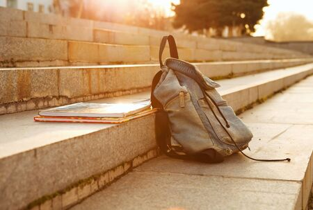 school bags: Old denim school backpack with copybooks left on the stone steps