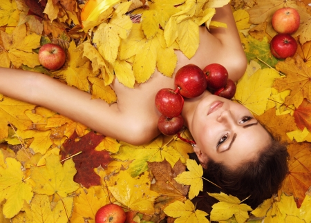 Beautiful girl Autumn lying over yellow leaves carpet photo