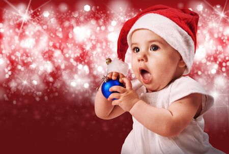 Dfde girl in santa's hat portrait over red shining background photo