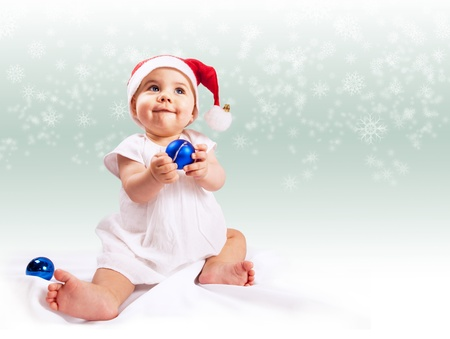 Funny baby girl in santas hat over light background with snowflakes photo