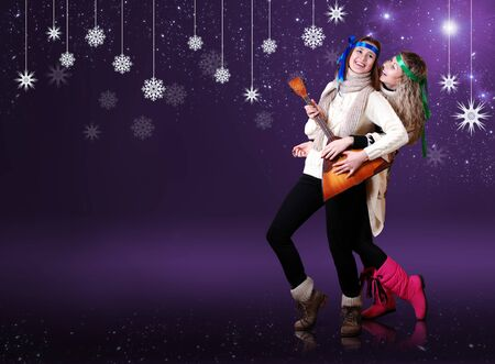 Beauty girls with balalika dancing over purple background with snow flakes photo