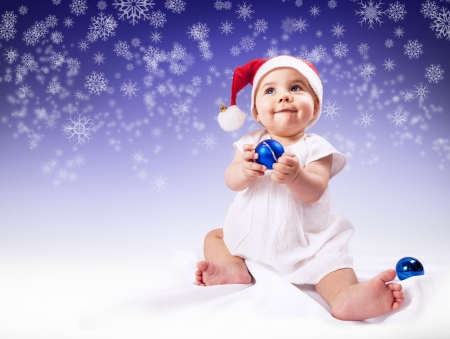 Funny baby girl in santas hat over dark blue background with snowflakes photo
