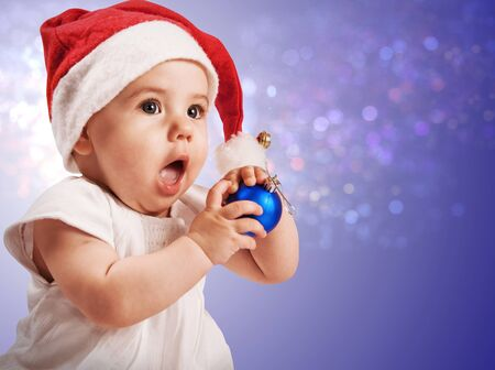 Pretty baby girl in christmas hat with blue ball  photo