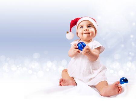 Baby girl in santas hat with blue ornament balls sitting over light blue background photo