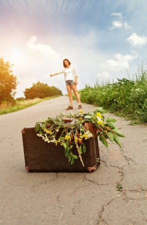hitchhiking: Hitchhiking girl traveller with old suitcase