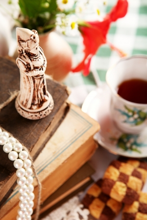 Still life with chess mini sculpture, old books, checkerboard cookies and cup of tea photo