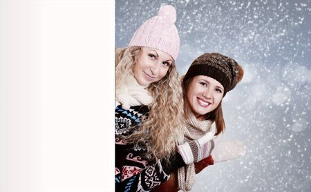 Two girlfriends looking out of white board over winter background photo