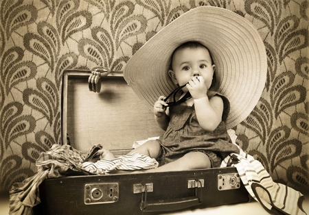 babydoll: Baby girl sitting into the old suitcase retro image
