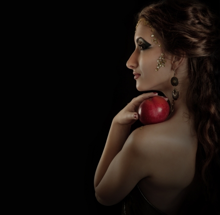 Portrait seductive posing girl with red apple over dark background photo