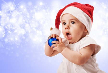Funny baby girl in santa's hat over blue background  photo