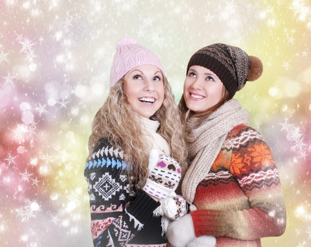 Two girlfriends happy with snowfall photo