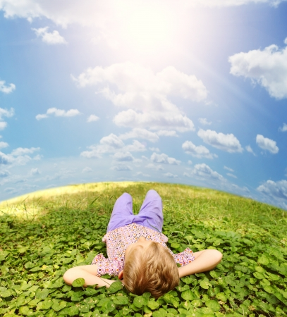 lying on grass: Carefree little boy lying on the green grass under blue sky Stock Photo