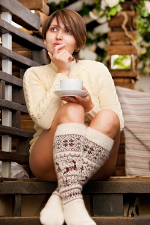 sweater girl: Beautiful woman with cup of coffee sitting at the stairs steps
