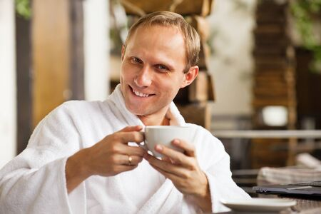 kindly: Kindly smiling handsome young man  with cup of morning coffee