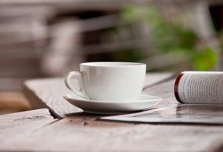 rustical: White cup with morning beverage and magazine on the wood table Stock Photo